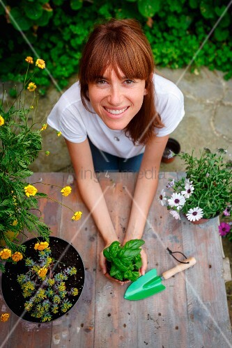 Woman holding basil plant and smiling at camera