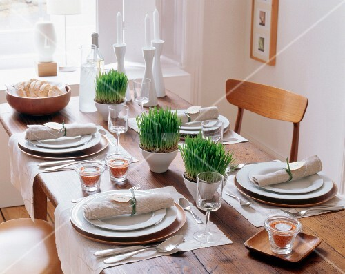 Set dining table decorated with grass, lentil-filled tealight holders and linen napkins
