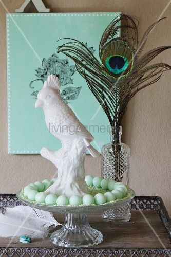 White chain cockatoo and string of turquoise beads on glass cake stand in front of peacock feather in vase