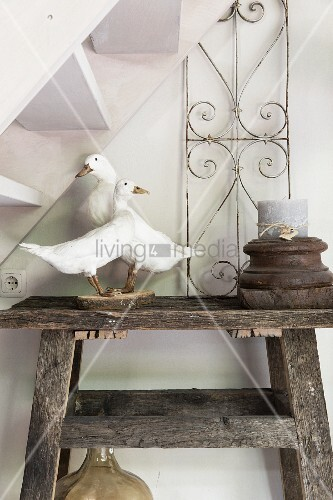 Stuffed geese and candle in wooden candle holder on rustic wooden table below staircase