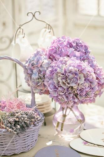 Bouquet Of Purple Hydrangeas In Glass Vase Next To Basket Of Dried