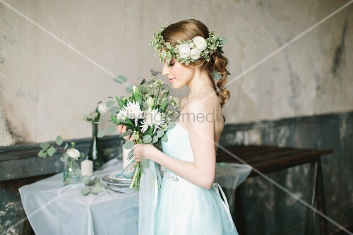 Fairy-tale bride holding bouquet and wearing flower wreath in vintage interior
