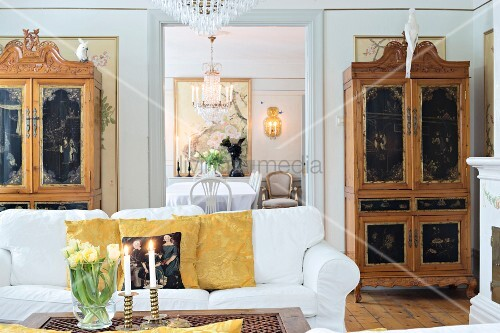 White sofa, antique cupboards with carved and painted panels in living room with view in to dining room through open doorway