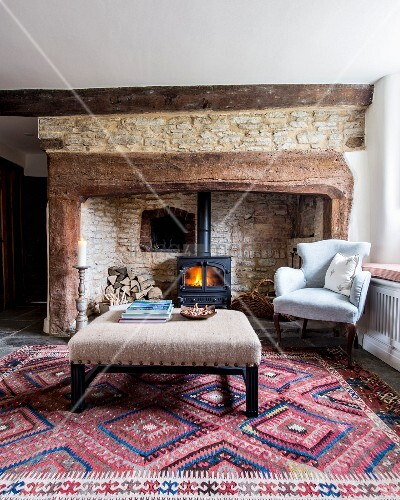 Ottoman and antique armchair in front of log-burner in old, stone inglenook fireplace