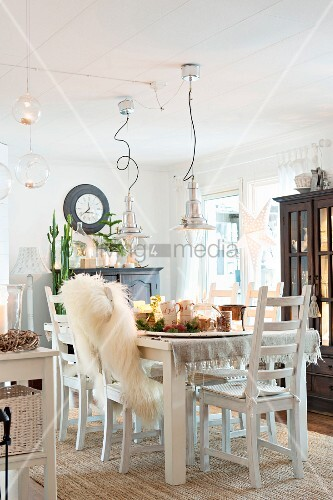 Set dining table and white chairs in cosily lit dining room