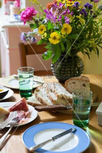 Sommerstrauss auf Tisch mit Brotzeit in Wohnküche
