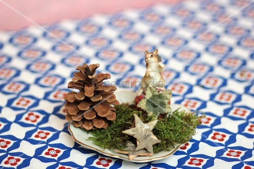 weihnachtliche tischdeko mit zapfen moos dekosternen tierfigur bild kaufen living4media. Black Bedroom Furniture Sets. Home Design Ideas