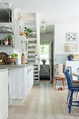 Rustic kitchen with wooden floor and white cabinets below staircase