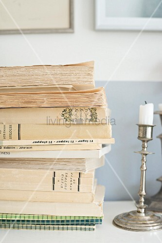 Stacked books and silver candlestick on shelf