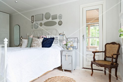 Antique armchair in corner next to door and double bed with white wrought iron frame in bedroom