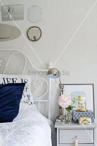 Bed with wrought iron frame and chrome table lamp on bedside table