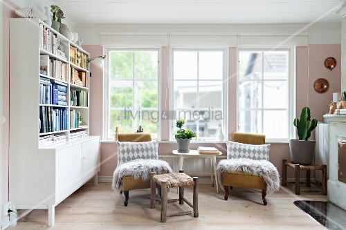 Patterned scatter cushions and fur blankets on two armchairs flanking side table below window and next to dresser with bookshelves