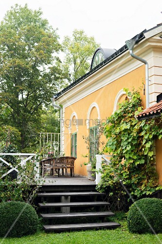 View from garden to steps and terrace outside traditional country house painted yellow with stucco façade elements