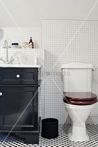 Toilet on black and white tiled floor next to black-painted washstand cabinet