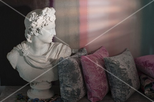 Bust of the god Apollo next to grey and pink velvet cushions on antique table