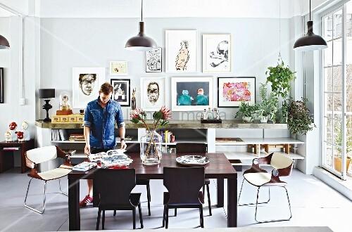 Mann am Essplatz mit dunklen Holzstühlen um modernem Tisch, im Hintergrund Bildersammlung an Wand über offenem Sideboard in Loft-Wohnung
