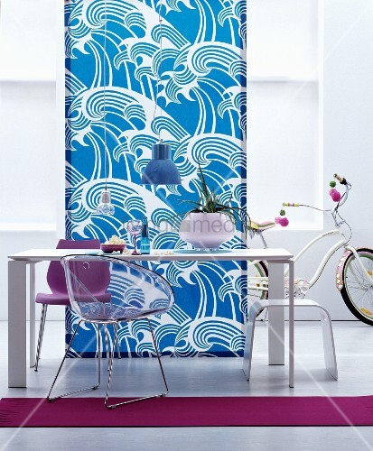 Simple white dining table, stool and chairs in front of length of fabric with pattern of stylised waves