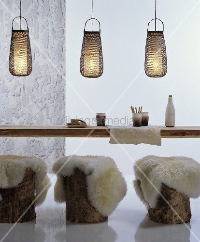 Sheepskin rugs on tree stump stools at rustic wooden table below decorative bamboo pendant lamps
