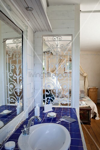 Washstand with blue-tiled counter next to partition between bathroom and bedroom