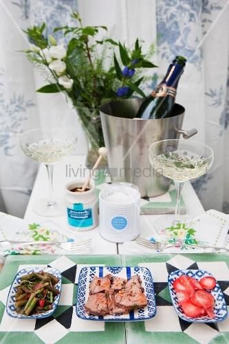 Champagne saucers, ice bucket and food arranged on garden table