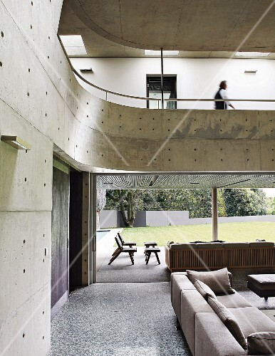 Living room with concrete gallery and walls and view of garden