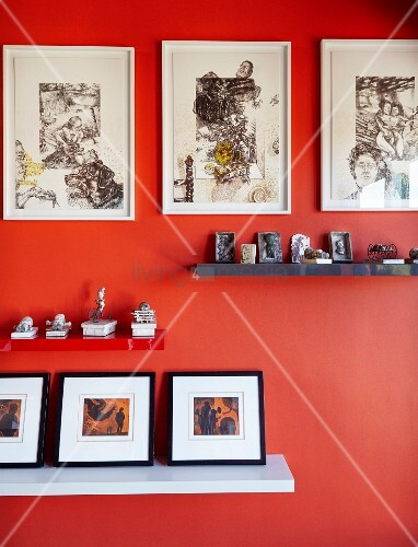 Collections of artworks on shelves and pictures on deep orange wall