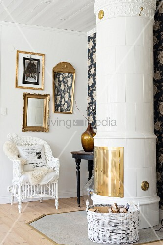 Gilt-framed pictures and mirror above white wicker armchair behind Swedish tiled stove