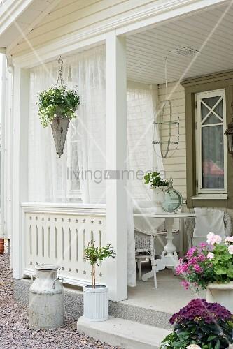 Flowers and curtains on veranda of Swedish house