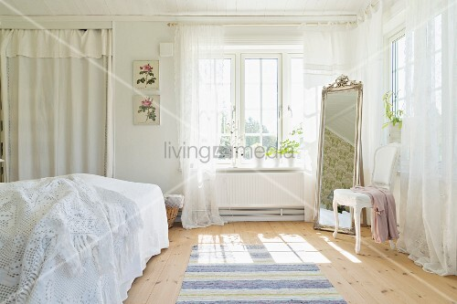 White curtains and cheval mirror in romantic bedroom