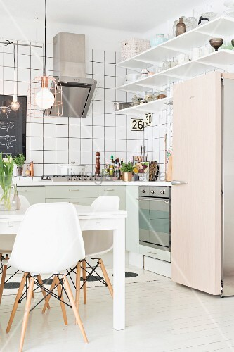 White classic chairs around table and retro fridge in open-plan fitted kitchen with white-tiled walls