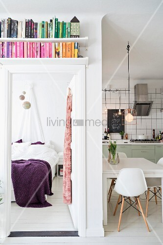 Bookshelves above open bedroom door and view of bed with purple bedspread; dining area in open-plan kitchen to one side