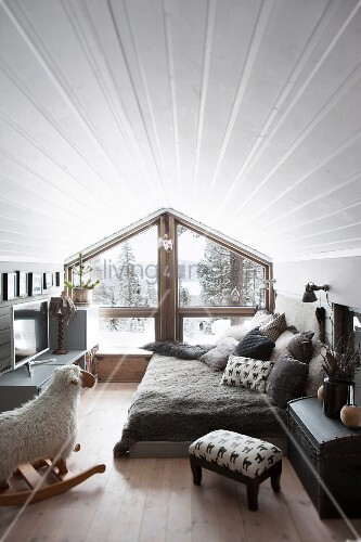 Pleasant attic room with white, wood-clad walls, rocking sheep. comfortable bed and glass gable-end wall