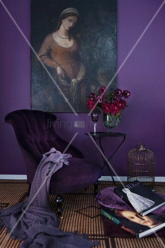 Sessel mit violettem Bezug und Tisch mit rotem Blumenstrauss vor auberginefarbener Wand mit Ölgemälde