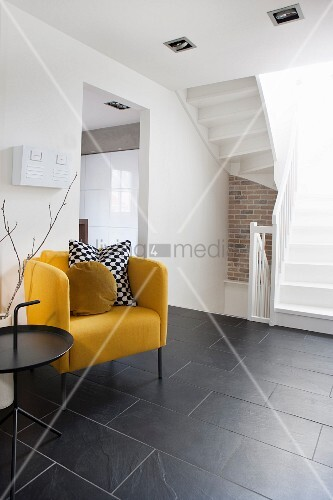 Yellow armchair providing a splash of colour in black and white hall