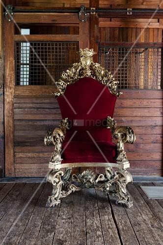 Opulent, ornate gilt throne with red velvet upholstery against board wall