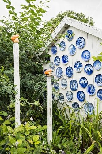 Weiße Holz-Giebelfassade dekoriert mit blauen Wandtellern im Garten mit Deko-Holzpfählen