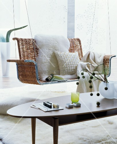 White sheepskin, cushion and blanket on cosy, wicker suspended bench in retro interior