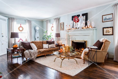 Sofa, armchair and brass and glass coffee table in front of festively decorated fireplace in American country-house living room