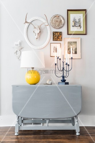 Table lamp with yellow base on grey-painted, drop-leaf console table below pictures and ornaments on wall