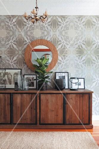 sideboard aus massivholz mit gerahmten fotos vor wand mit optic art tapete und aufgeh ngtem. Black Bedroom Furniture Sets. Home Design Ideas