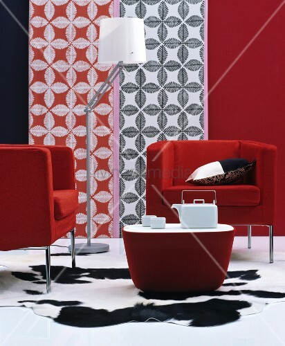 Elegant, red designer armchair, matching coffee table and white tea service on black and white animal-skin rug in front of decorative wall panels