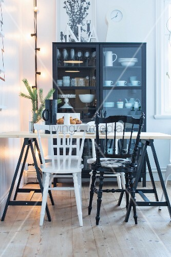 Dining table and various black and white chairs in front of crockery in display case