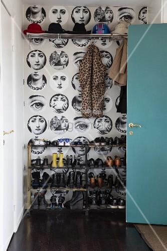 Turquoise door and coat rack in hallway with Fornasetti wallpaper