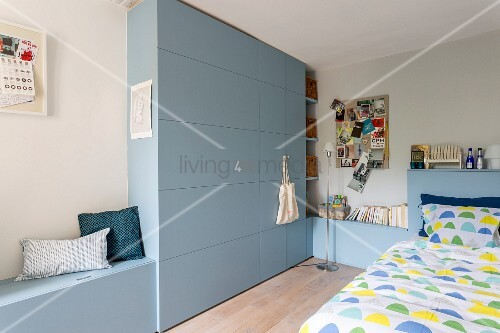 Fitted cabinets with integrated storage bench, fitted cupboards and bed headboard painted blue