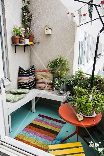 Holzbank mit Kissen und Blumentöpfe auf Balkon