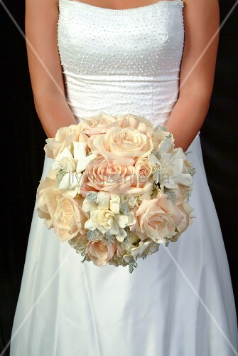 Bride holding bouquet of roses and gardenias