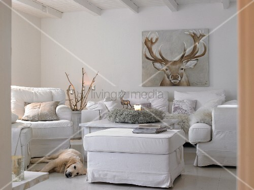 White upholstered furniture, picture of reindeer and dog in wintry living room