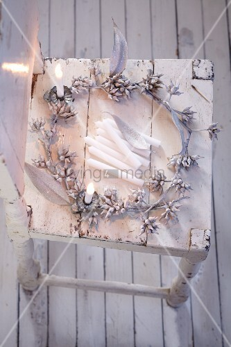 A shiny silver eucalyptus wreath on a white wooden chair