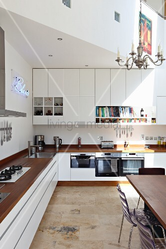L-shaped kitchen counter with wooden worksurface and wall units with doors and open-fronted modules below gallery