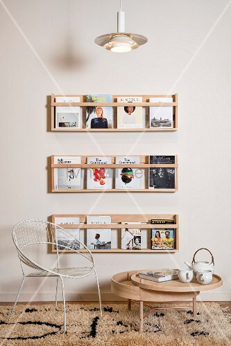 White retro metal chair and low, wooden round table with swivelling tray below books displayed on wall-mounted shelves